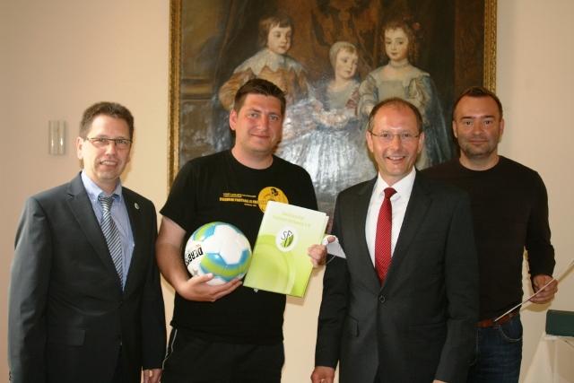 Jörg Gernhardt (Sächsischer Fußballverband) und Sächsischer Staatsminister Markus Ulbig übergeben den DSC'ern Benjamin Kümmig und Marcus Zillich die Urkunde